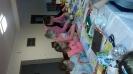 Dzieci i rodzice wykonują własnoręcznie kartki świąteczne w nowym domu parafialnym